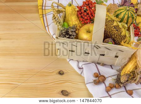 Autumn arrangement in a basket on wooden table - Lovely autumn decoration with all sorts of pumpkins corn grain sunflower and forest fruits set in a basket on a towel and a wooden table.