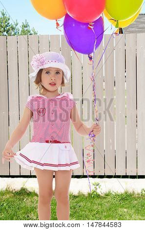 Adorable little girl holding colorful balloons. A girl in a short pink dress and white hat with pink bow.Closeup.On the background of beautiful wooden fence.