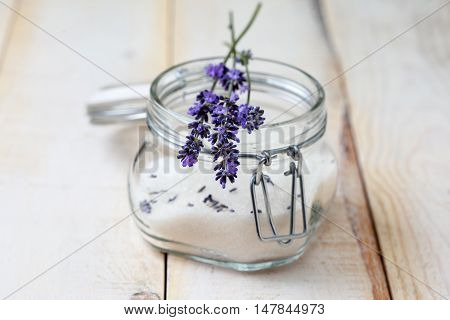 small bouquet of lavender on a jar of lavender sugar on a light wooden background