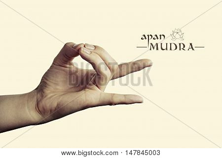 Image of woman hand in apan mudra. Gesture is isolated on toned background.