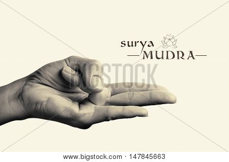 B/W image of woman hand in Surya mudra. Gesture is isolated on toned background.