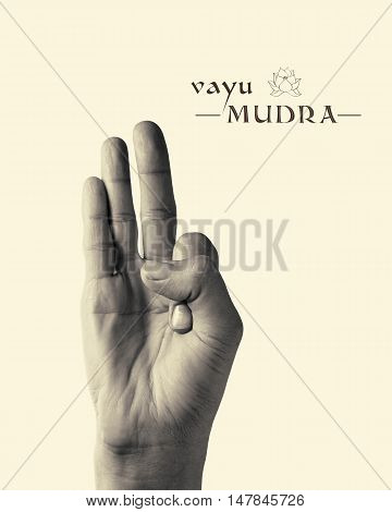 B/W image of woman hand in Vayu mudra. Gesture is isolated on toned background.