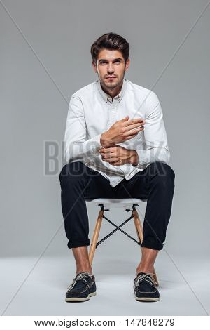 Handsome relaxed man unbuttoning shirt sleeve and sitting on the chair over gray background