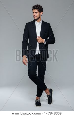 Full-length portrait of a handsome businessman isolated on a gray background