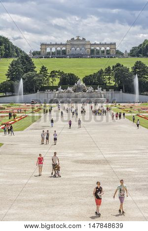 VIENNA, AUSTRIA, JULY 4,2016: People walking at the gardens of Schonbrunn Palace, a former imperial summer residence of Habsburg monarchs, Gloriette can be seen on the background.