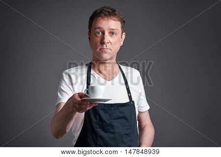 A middle age man serve a cup of coffee
