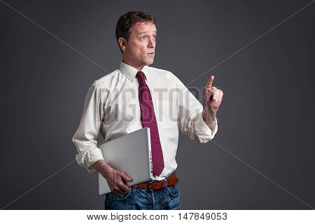 A middle age man standing with a laptop and talking to someone