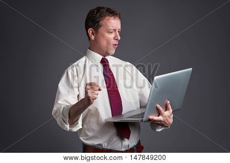 A middle age man standing and using a laptop and feeling happy.