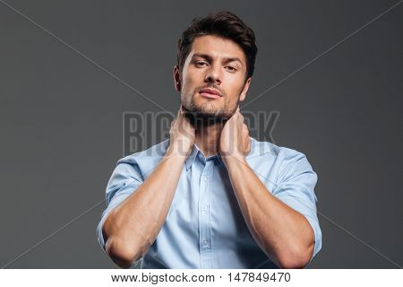Portrait of a young tired businessman with eyes closed having neck pain isolated on a gray background