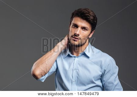 Portrait of a young tired businessman having neck pain isolated on a gray background