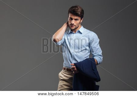 Portrait of a young businessman holding jacket having neck pain isolated on a gray background