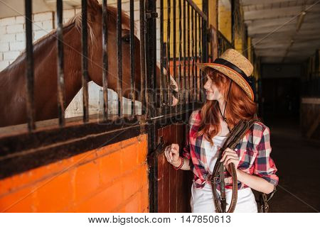 Pretty redhead young woman cowgirl standing and looking at horse in stable