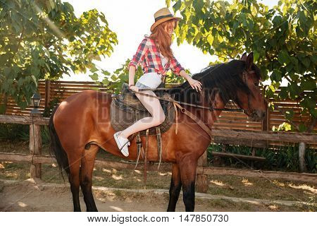 Happy redhead young woman cowgirl smiling and riding horse