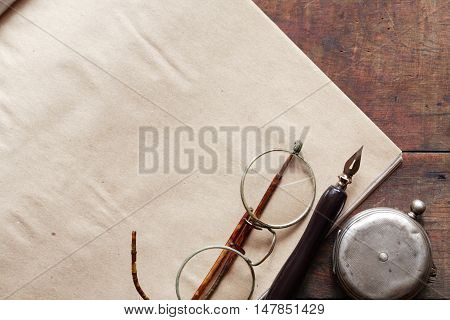Old spectacles near pocket watch and pen on paper background
