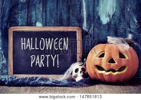 a chalkboard with the text Halloween party, placed on a rustic wooden surface next to a skull and a carved pumpkin covered with spiders and cobwebs