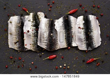 closeup of some raw sardine fillets on a slate surface, spiced with peppercorns and chili pepper