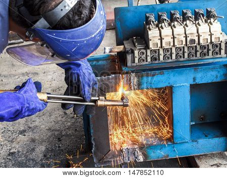 Worker cut steel large box with light.