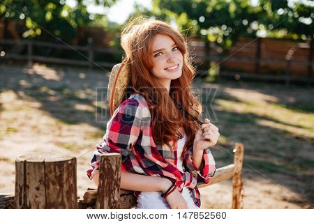 Closeup of cheerful beautiful young woman cowgirl on ranch