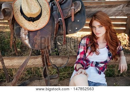 Portrait of beautiful redhead young woman cowgirl sitting outdoors