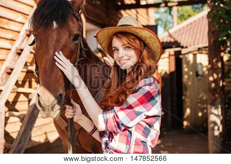 Happy redhead young woman cowgirl with her horse in village