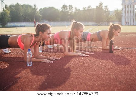 Group of fit women doing planking exercise in the stadium
