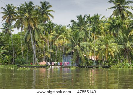 ALLEPPEY KERALA INDIA - AUGUST 16 2016: Unidentified indian people in small boat in backwaters. Kerala backwaters are both major tourist attraction and integral part of local people life in Kerala