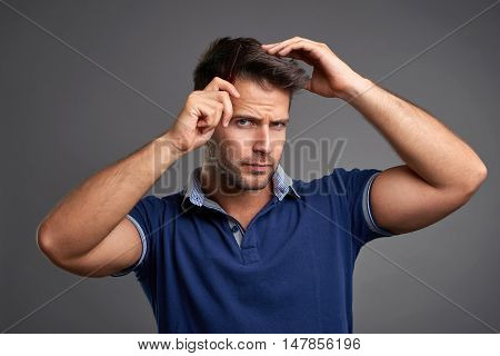 A serious handsome young man combing his hair