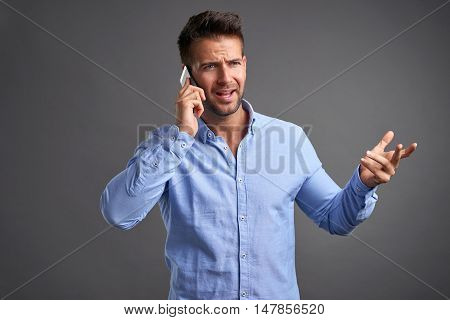 A handsome young man feeling upset while talking on a smartphone