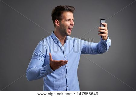 A handsome young man screaming to a smartphone in his hand