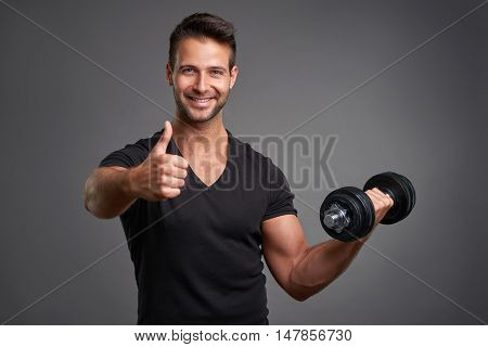 A handsome young man lifting weight smiling and showing thumbs up