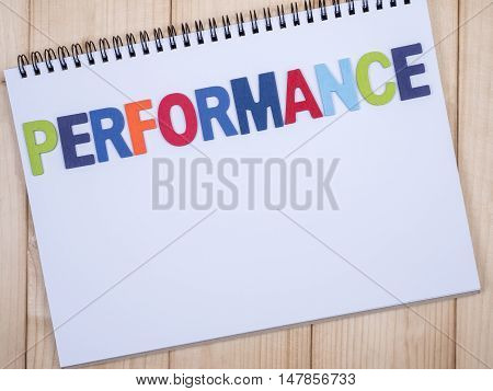 Word spelling Performance on white notebook with wood background (Top view)