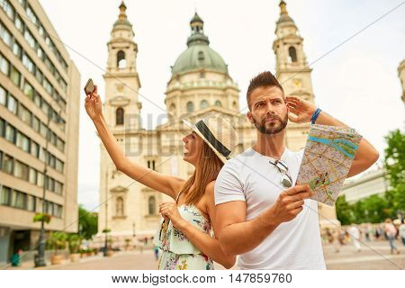 A handsome young man is feeling confused and looking around while his beautiful girlfriend is taking selfies at the St. Stephens Basilica in Budapest, Hungary.