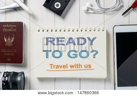 Ready to go travel with us travel agency banner on book and travel objects.