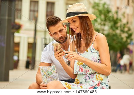A beautiful young couple are sitting and using a smartphone at the Egyetem Square in Budapest, Hungary.