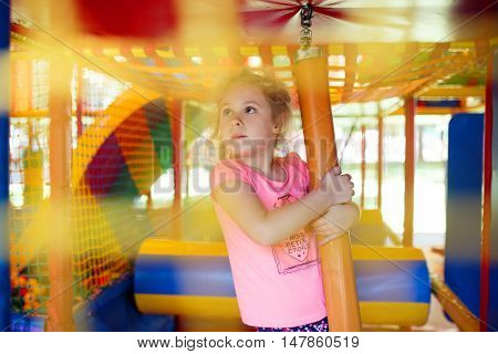 Cute little girl have fun at soft outdoor playground.