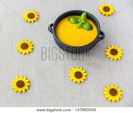 Brown Ceramic Bowl filled with Butternut Squash Soup positioned in top right corner and decorated with handmade sunflowers.