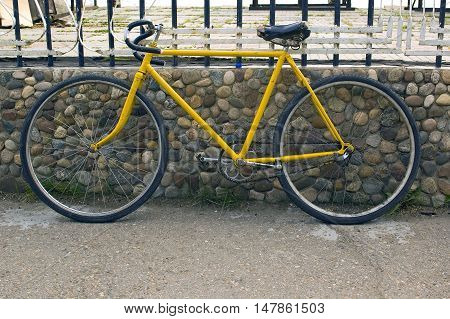 Old yellow bike leaning on the wall.