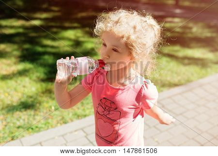 Little girl with bottle of mineral water, summer outdoor.
