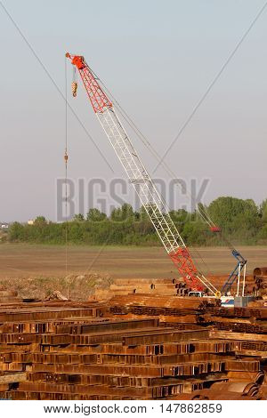Metal scrap yard with heavy crane and pile of rusted steel