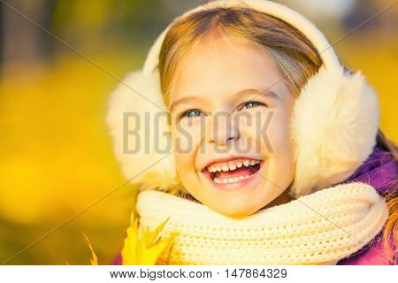 Happy little girl in earflaps in the autumn park