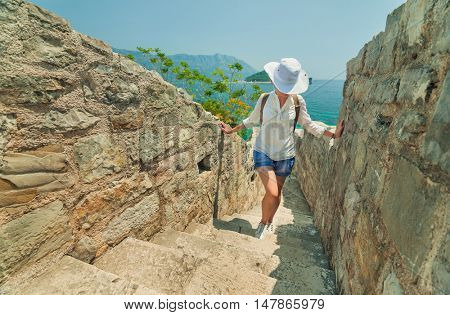Young girl tourist standing by the sea on a background of mountains on a sunny day. Budva, Montenegro.