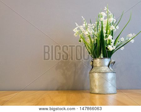 White spring flowers in vintage galvanized vase on wood table and cement wall in background with copy space.
