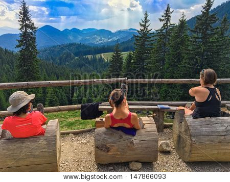 Zarnesti, Romania - September 16, 2016: Tourists woman relaxing at the famous cottage refuge Curmatura, in Piatra Craiului mountain