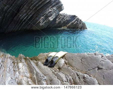 flippers for diving and the azure water of the sea rocky coast strong wave-clear Adriatic sea summer blue sky lovely stay in a clean area