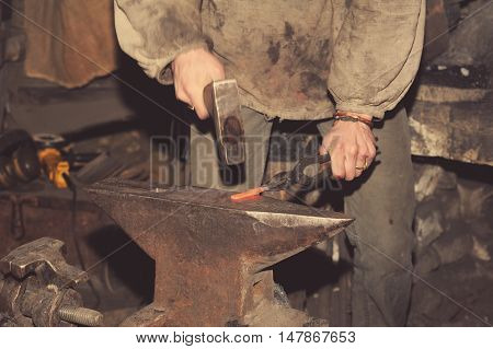 Blacksmith working metal with hammer on the anvil in the forge