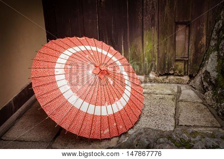 A decorate Japanese parasol left outside of the house. Retro style with intentional vignette.