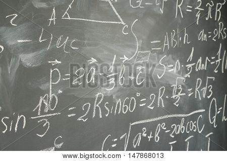 side view of math formulas written in white chalk on black board background