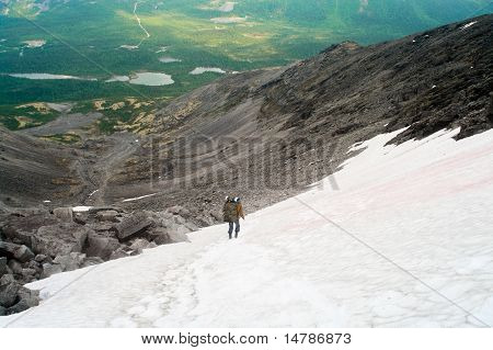 Man With Backpack Standing On Snow In Mountains