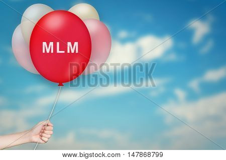 Hand Holding MLM or Multi level marketing Balloon with sky blurred background