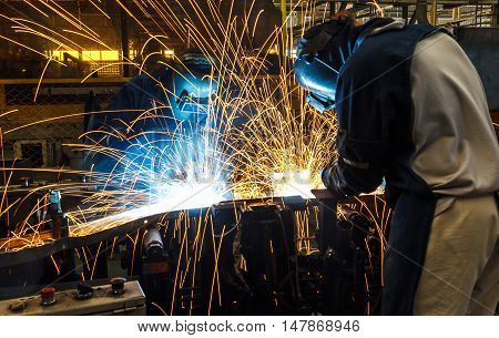 The Team worker with protective mask welding.